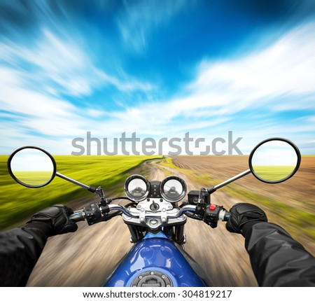 Man driving on moto on big speed on country road - stock photo