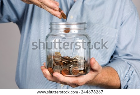 Man drops money into a glass jar for a savings account. - stock photo