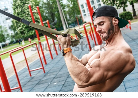 Man during workout with suspension straps on the street - stock photo