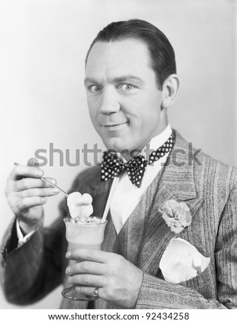 Man eating an ice-cream out of a glass with a straw - stock photo