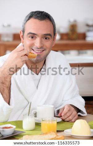 Man eating breakfast in your bathrobe - stock photo