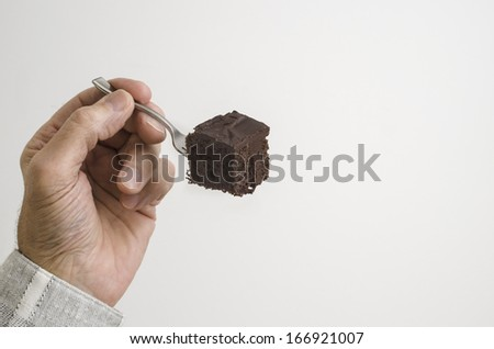 man eating piece of chocolate cake with tiny fork - stock photo