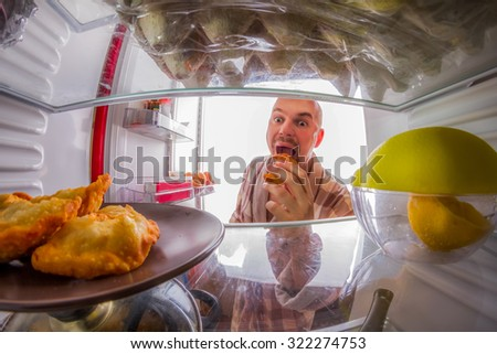 Man eats bread rolls, the view from the refrigerator - stock photo