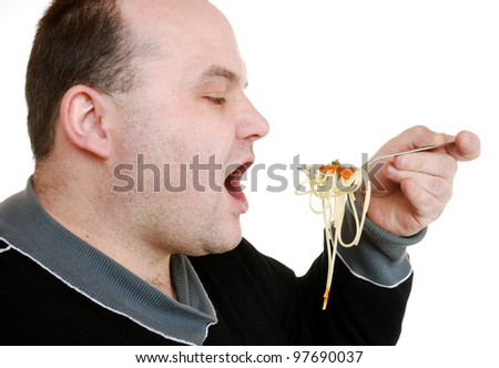 man eats spaghetti with tomato sauce - stock photo