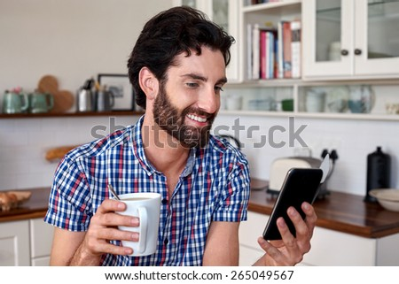 man enjoying coffee with mobile cellphone at home kitchen - stock photo