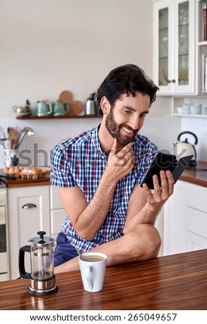 man enjoying french press filter coffee with mobile cellphone at home kitchen - stock photo