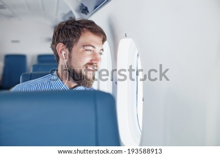 Man enjoying his journey by airplane - stock photo