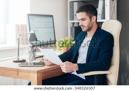 Man examining documents. Side view of confident young man examining document while sitting at his working place in office - stock photo