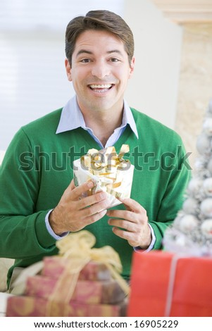 Man Excited To Open Christmas Present - stock photo