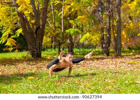 Man exercises in the autumn forest yoga tittibhasana pose - stock photo