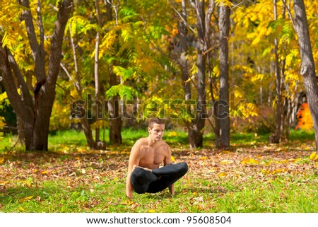 Man exercises in the autumn forest yoga uth pluthi pose - stock photo