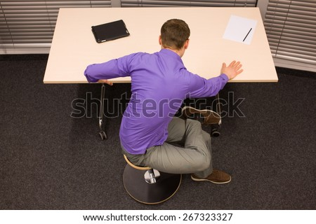 man exercising during short break in work at his desk in office  - stock photo