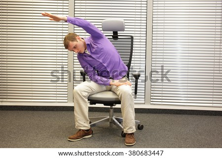 man exercising on chair in office, healthy lifestyle - front view - stock photo