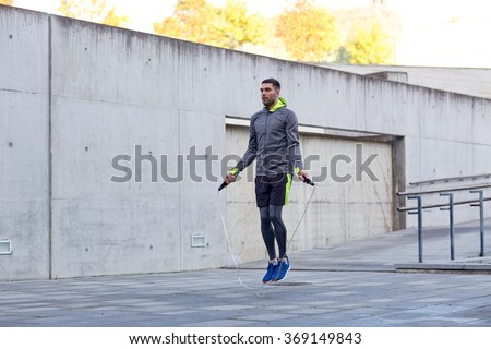 man exercising with jump-rope outdoors - stock photo