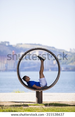 Man exercising with sit ups at Lisbon, next to the river - stock photo