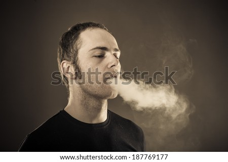 Man exhales smoke on dark background. Closeup - stock photo