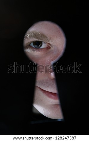 Man eye looking through hole in keyhole, on black background - stock photo