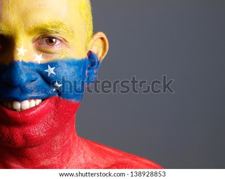 Man face painted with venezuelan flag. The man is smiling and photographic composition leaves only half of the face. - stock photo