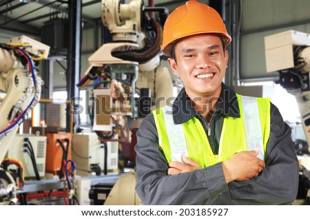 Man factory engineer or worker with robot machine inside modern industrial manufacturing, automobile industry - stock photo