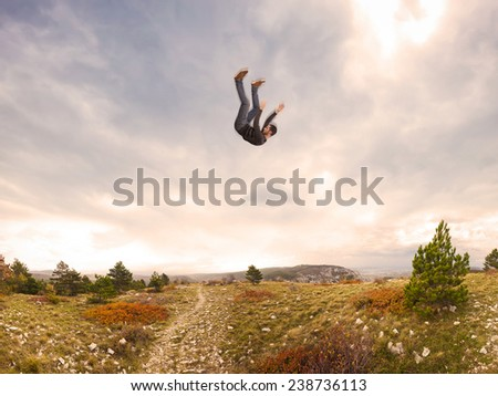 man falling down from the sky in autumnal landscape - stock photo