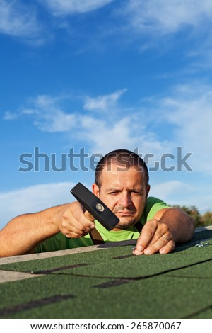 Man fastening bitumen roof shingles with nails and hammer - copy space - stock photo
