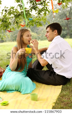 Man feeding a woman under a tree cake - stock photo