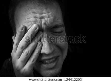 man feeling upset, crying with hand on head with black background - stock photo