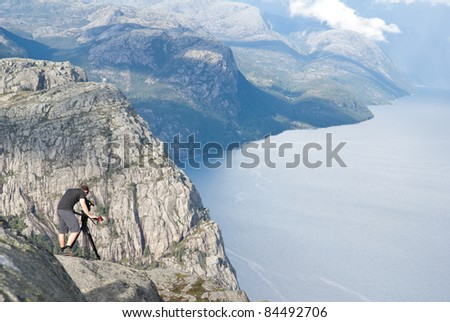 man filming the lysefjord in Norway - stock photo