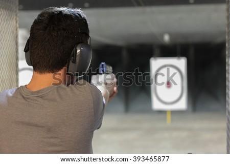 man firing usp pistol at target in indoor fining range - stock photo