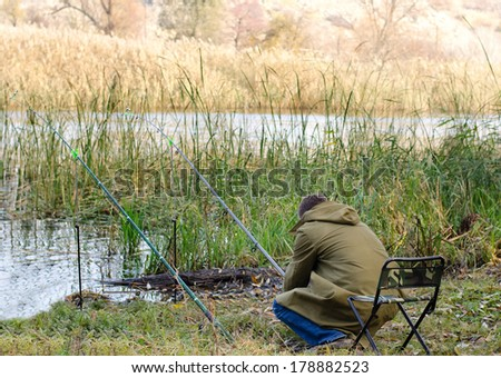 Man fishing at the side of a tranquil lake sitting comfortably in a chair alongside reeds with his rods set up in front of him - stock photo