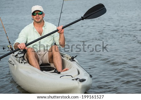Man fishing from kayak on a beautiful day at dusk, closeup. - stock photo