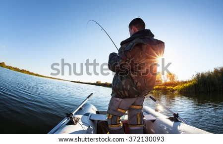 Man fishing from the boat on the autumn lake - stock photo