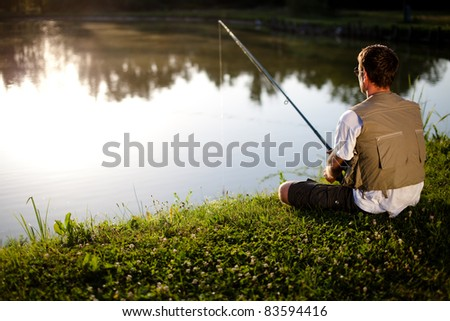 Man fishing in a pond. Back view. Shallow DOF. - stock photo