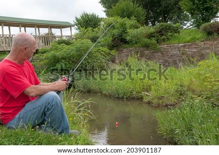 Man fishing in small creek - stock photo
