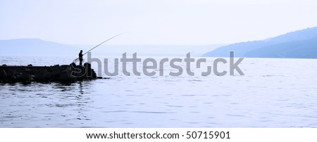 Man fishing in the sea - stock photo