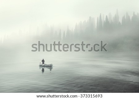 Man fishing on a boat in a mystic foggy lake - stock photo