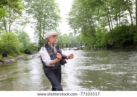 Man fishing trout in river - stock photo