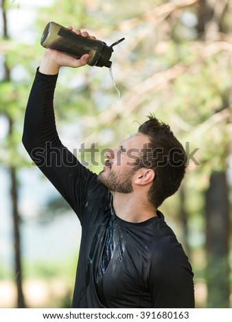 Man fitness runner drinking and splashing water in his face. Funny image of handsome male refreshing during workout - stock photo