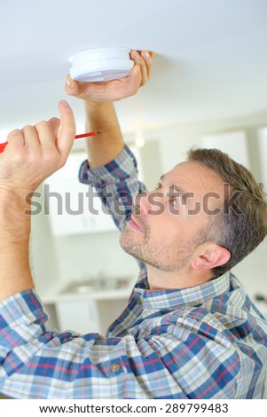 Man fitting a smoke alarm - stock photo