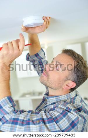 Man fitting a smoke alarm - stock photo
