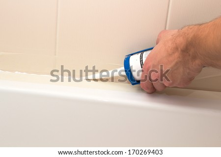 Man fixing bath in washroom with silicone - stock photo
