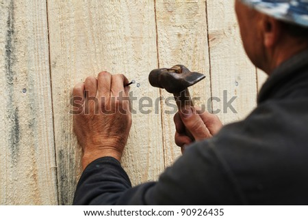 Man fixing wooden plank with a nail - stock photo