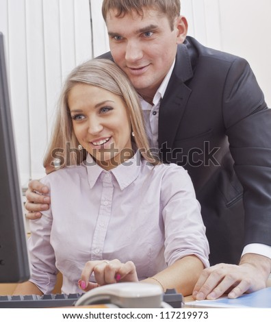 man flirting with a woman in the workplace - sexual harassment boss with his secretary - stock photo