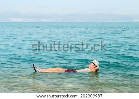 Man floating in a glassy water of dead sea with outstretched arms  - stock photo