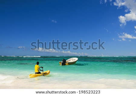 Man floats canoe in the direction of the drifting boat - stock photo