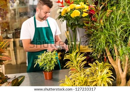 Man florist reading price bar-code reader flower shop plant - stock photo