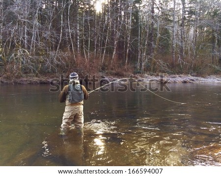 Man Fly Fishing in Cold Winter Weather - stock photo