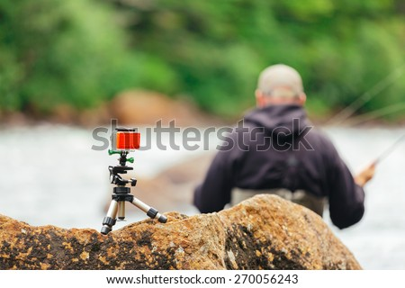 Man Fly fishing on Jacques-Cartier river with go-pro, in Parc national de la Jacques-Cartier, Quebec. - stock photo