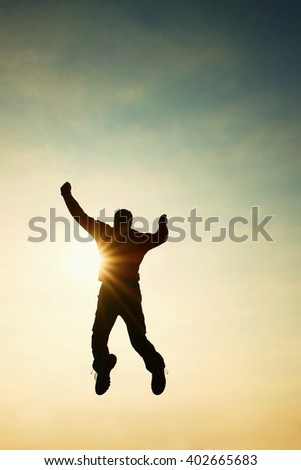 Man fly in air. Man falling down with hands up. Sun and colorful sky background. Vintage Style Toned effect - stock photo