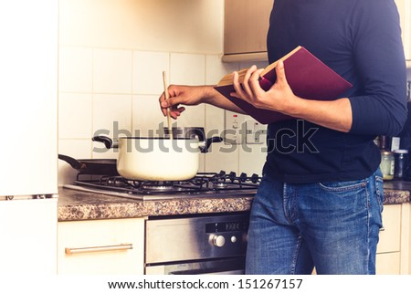 Man following a recipe and stirring his pot - stock photo